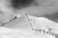 在滑雪倾斜和驾空滑车的黑白看法在太阳冬天m 库存照片