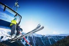在滑雪吊车的滑雪者选址-增强在晴天和山 免版税库存图片