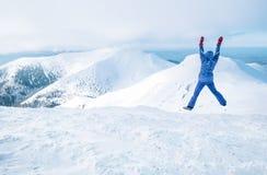 在滑雪温暖的衣物穿戴的妇女广角射击跳跃在与多雪的范围的在背景的山峰和谷 库存图片