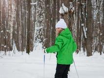 在滑雪的女孩骑马在冬天森林里落日 免版税库存照片