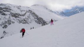 在滑雪者附近的运动他们在困难山陡坡的滑雪 股票录像
