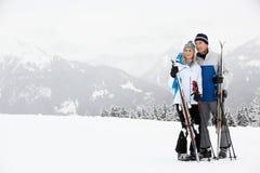 在滑雪节假日的中世纪夫妇在山 免版税库存照片