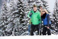 在滑雪节假日的新夫妇在山 免版税库存图片