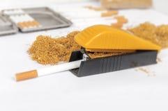 在滚轧机和金属烟草箱子的一根香烟 库存照片