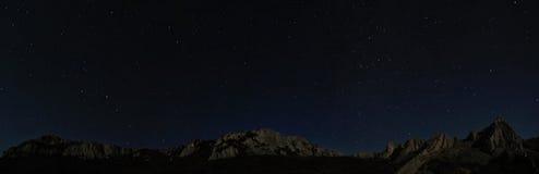 在满天星斗峭壁晚上岩石的天空之上 免版税图库摄影