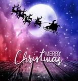 在满月和屋顶上面的圣诞老人飞行 库存照片