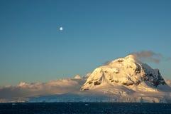 在满月,南极洲下的被环绕的被日光照射了山峰 库存照片