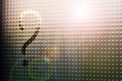在满身是汗的玻璃窗的被弄脏的问号 免版税库存照片