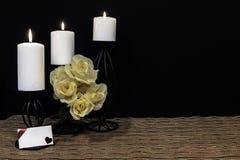 在滤网位置字块的黑蜡烛台栖息的黄色玫瑰、白色蜡烛和与卡片的木桌美好的bouquie和 图库摄影