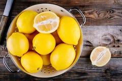 在滤锅的新鲜的有机柠檬在木背景 顶视图 免版税图库摄影