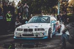 在漂泊展示的BMW 3系列driftcar灼烧的轮胎 图库摄影