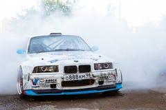 在漂泊展示的BMW 3系列driftcar灼烧的轮胎 免版税库存图片