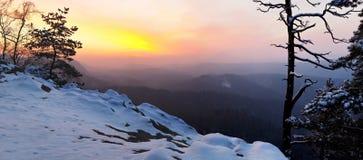 在漂泊撒克逊人的瑞士公园砂岩岩石的冬天破晓。从岩石峰顶的看法在谷。 库存图片