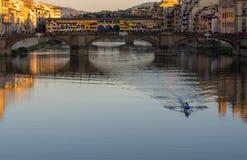 在漂浮在圣三位一体桥梁和Ponte Vecchio附近的亚诺河的皮船 免版税库存图片