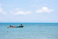 在漂浮在有明亮的天空的海的左边的地方渔夫小船在背景中下午在酸值Mak海岛 库存照片