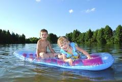 在漂浮在气垫的河男孩和女孩的夏天。 免版税库存图片