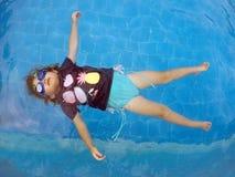 在漂浮在水池的观点的一个女孩上 免版税图库摄影