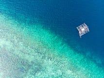 在漂浮在绿松石珊瑚礁热带加勒比海的看法传统渔船下的空中上面 印度尼西亚摩鹿加群岛 免版税库存图片
