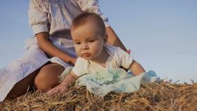 在演奏一件蓝色礼服的白色衬衣的逗人喜爱的孩子c年轻母亲在干草堆在夏天 使用的妇女抱着婴孩 影视素材