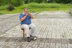 在演奏木管乐器sopilka的街道上的孤独的音乐家 免版税库存照片