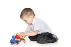在演奏玩具白色的男孩起重机 免版税库存照片