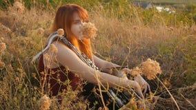 在演奏saxophoneon自然,妇女的日落年轻美丽的红发女孩的剪影吹入管子,概念爱好,mus 股票录像