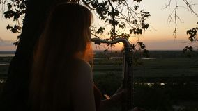 在演奏saxophoneon自然,妇女的日落年轻美丽的红发女孩的剪影吹入管子,概念爱好,mus 影视素材