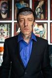 在演播室刺字在黑夹克和蓝色衬衣的大师 库存照片