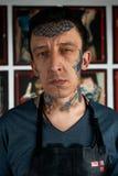 在演播室刺字黑皮革围裙的艺术家 库存照片