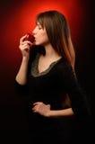 在演播室吃一个红色苹果的美丽的女孩 库存照片