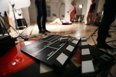 在演播室摄制电影背景、clapperboard和录影光 库存照片