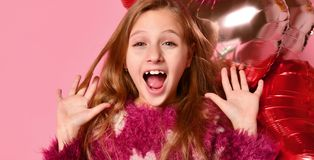 在演播室,广泛微笑和使用与桃红色气球的逗人喜爱的女孩特写镜头 她穿毛线衣和牛仔裤 免版税图库摄影