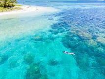 在潜航在珊瑚礁热带加勒比海,土耳其玉色水的人下的空中上面 印度尼西亚巴尼亚群岛苏门答腊, 库存照片