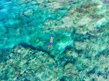 在潜航在珊瑚礁热带加勒比海,土耳其玉色水的人下的空中上面 印度尼西亚Wakatobi群岛, 库存照片