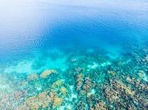 在潜航在珊瑚礁热带加勒比海,土耳其玉色水的人下的空中上面 印度尼西亚Wakatobi群岛, 免版税库存图片