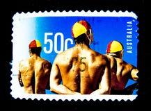 在澳大利亚打印的邮票显示三个人站立在价值的海滩救生员的图象在50分 免版税库存照片