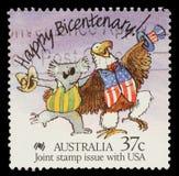 在澳大利亚打印的邮票显示愉快的二百周年!澳大利亚考拉和美国白头鹰讽刺画  库存照片