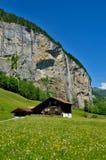 在瀑布下的木木材房子在阿尔卑斯 免版税库存图片