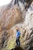 在瀑布下的登山家 库存图片