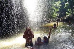 在瀑布之下的人们 免版税库存照片