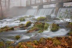 在瀑布之下的桥梁秋天有雾的早晨 免版税库存图片