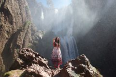在瀑布前面的嬉皮旅游制造的和平标志 免版税库存图片
