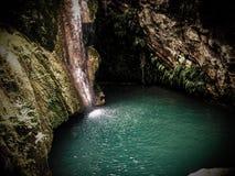 在瀑布后的神秘的洞 库存照片