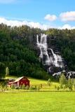 在瀑布旁边的红色农场。 库存照片