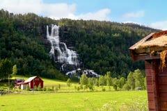 在瀑布旁边的农场在挪威 免版税图库摄影