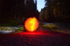 在瀑布旁边的发光的红色天体 免版税库存图片