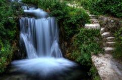 在瀑布旁边的步在绿色庭院里 库存照片