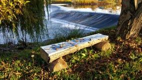 在瀑布旁边的长木凳 免版税库存照片