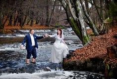 在瀑布的背景的一对年轻夫妇 免版税图库摄影