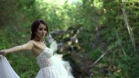 在瀑布附近的新娘盘旋的和挥动的礼服 影视素材